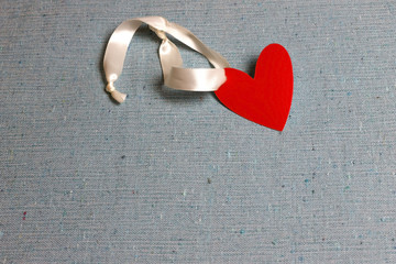 Red heart on a ribbon on canvas. Valentine's Day. Copy space for text. Card design.
