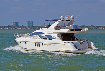 White motor yacht cruising the florida intra-coastal waterway off Miami Beach.