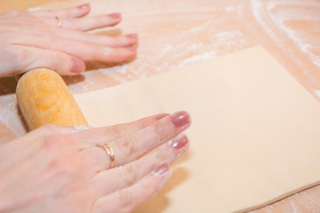 The girl rolls out the dough