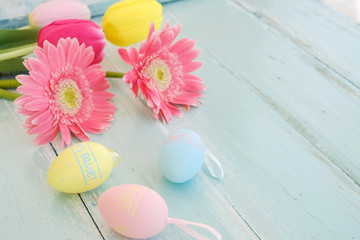 Wall Mural - Colorful Easter eggs with flower on rustic wooden planks background. Holiday in spring season. vintage pastel color tone. Close-up composition.