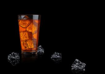 Orange energy soda drink glass with ice cubes