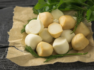 Freshly prepared smoked and regular mozzarella cheese in paper on a wooden table.