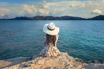 Wall Mural - Young woman sitting on the top of rock and looking at the seashore.