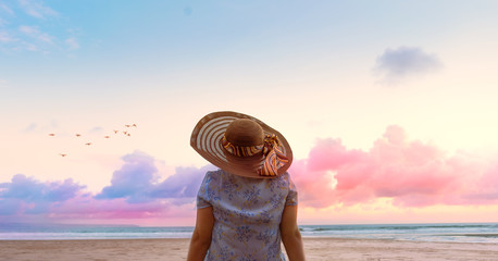 Relaxing woman sitting on the beach looking at sea and sky with hat. Dream travel and vacation concept. Can be used for banner