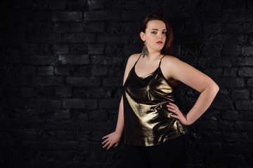 plus size model in a gold blouse and black jeans on a brick loft background.
