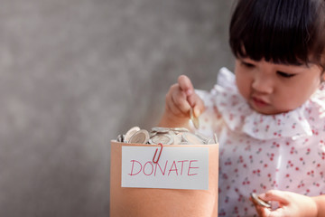 Child with Donation Concept. 2 Years Old Child putting Money Coin into a Donate Box