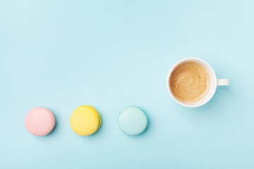 Coffee and colorful macaron on pastel blue background top view. Cozy morning breakfast. Fashion flat lay style. Sweet macaroons.