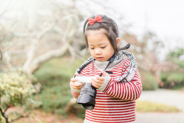 Cute little asian girl takes picture with mirrorless camera in winter in Japan garden.