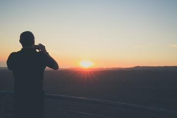 The man is taking the picture of sunset by his smartphone.