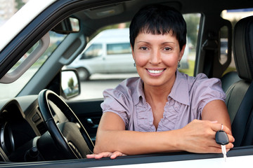 Senior woman car driver holding a key and smiling to you