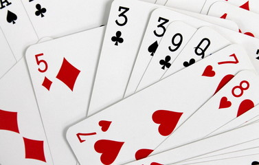 Playing cards of different suits scattered randomly close up.