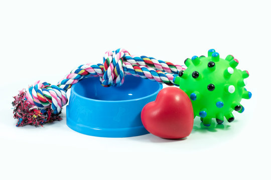 Pets are friends concept.  Pet bowl and rubber toys with rope for dog or cat isolated on white background.