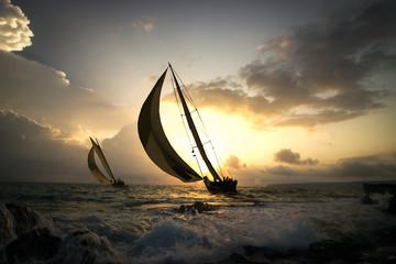 deux voiliers naviguent au soleil couchant