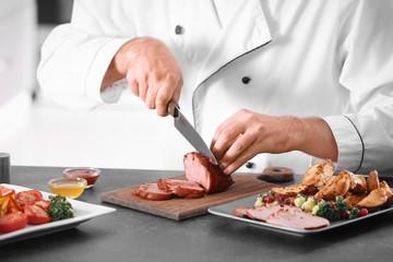 Chef slicing yummy honey baked ham on wooden board
