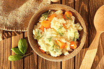 Dish with delicious pumpkin risotto on wooden table