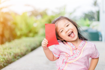 Happy Little asian girl in chinese traditional dress smiling and holding red envelope.Happy chinese new year concept.