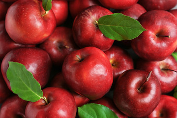 Fresh ripe red apples with green leaves as background
