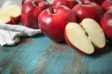 Ripe red apples on color wooden table, closeup