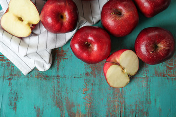 Ripe red apples on color wooden table