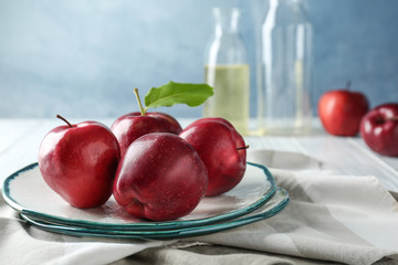 Plate with ripe red apples on table