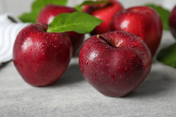 Ripe red apples with green leaves on table, closeup