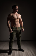 Strong athletic muscular man on dark background
