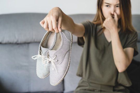Young woman holding a pair of smelly shoes