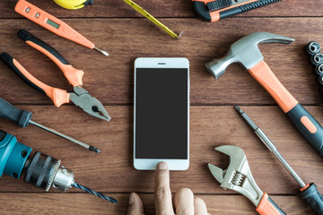 Tools and smart phone on wooden background
