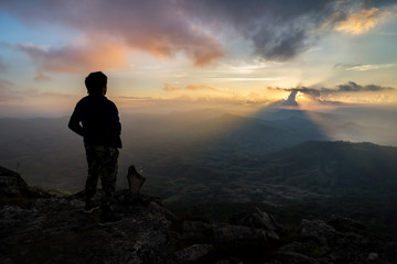 Young man hiker relaxing on top of a mountain at sunset