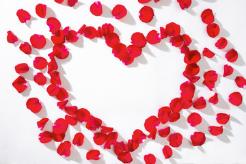 Heart of red rose petals on white background.