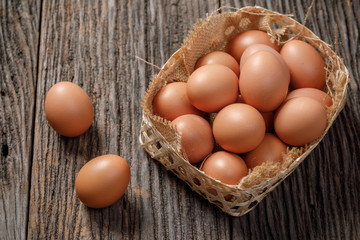 Brown Egg in a basket on wooden table, Chicken Egg
