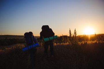 Silhouettes of two hikers with backpacks walking at sunset. Trekking and enjoying the sunset view