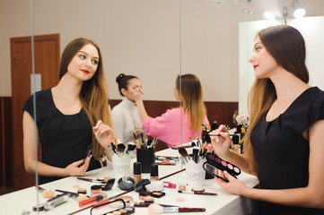 A professional make-up artist prepares to work in front of a mirror
