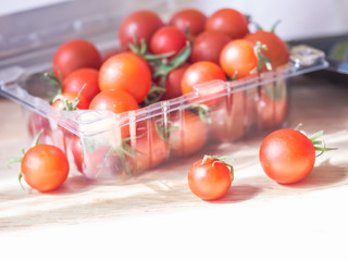 Vivid red tomatoes in plastic box on the table in the kitchen. Dieting or healthy concepts.