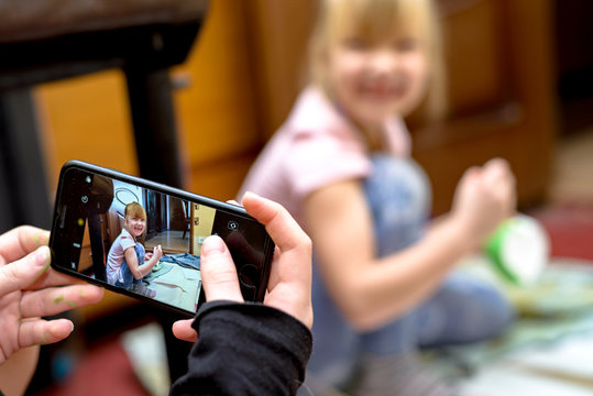 A cheerful child is photographed on a smartphone