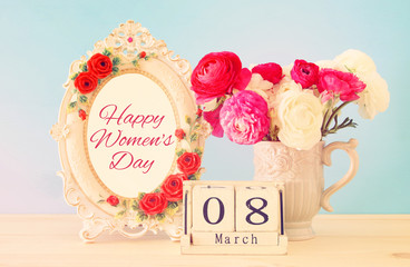 International women day concept with beautiful flowers in the vase and date on wooden table.
