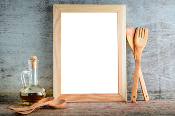 empty wooden frame with isolated white background and kitchen utensils on a wooden background