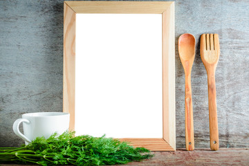 empty wooden frame with isolated white background and kitchen utensils and green dill on a wooden background