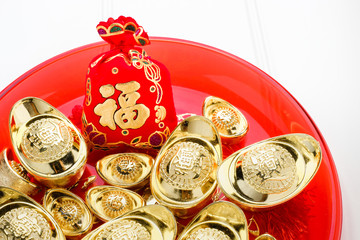 Chinese New year ang pow red felt fabric bag with gold ingots in red tray on white wood table top,Chinese Language on bag mean Happiness and on ingot mean wealthy.