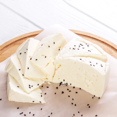 Feta cheese with sesame seeds. Top view. Square. The concept is healthy food, vegetarianism, farm.