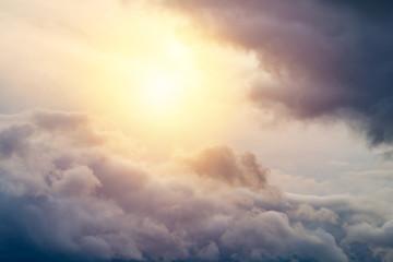Sun shines through a gray thunder clouds