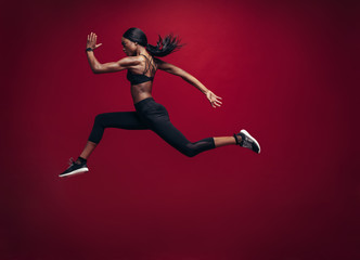 Female athlete running and jumping Wall mural