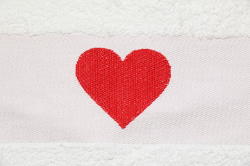 Embroidered red heart on a white background