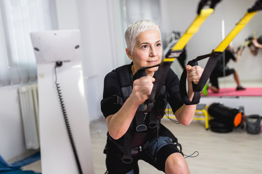 Beautiful senior woman doing exercises in center for physical rehabilitation.