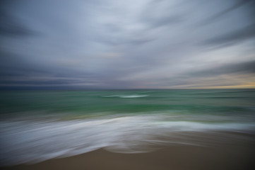 Abstract defocus motion blur background of waves crashing on a tropical beach with stormy weather on the horizon