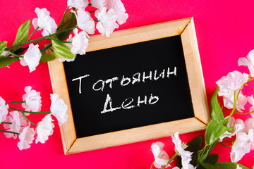 The inscription in Russian: Tatyanin day. Russian holiday on student's day. A chalk plaque surrounded by white flowers on a pink background.