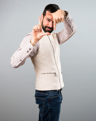 Handsome man with vest focusing with his fingers on grey background