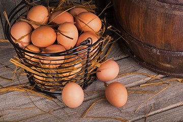 Brown Chicken Eggs in a Basket and On a Rustic Wooden Surface