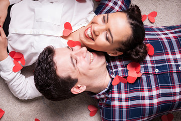 Top close up view on couple lying on the floor covered with small red hearts
