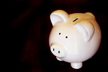 Piggy bank on a black background with copy space.